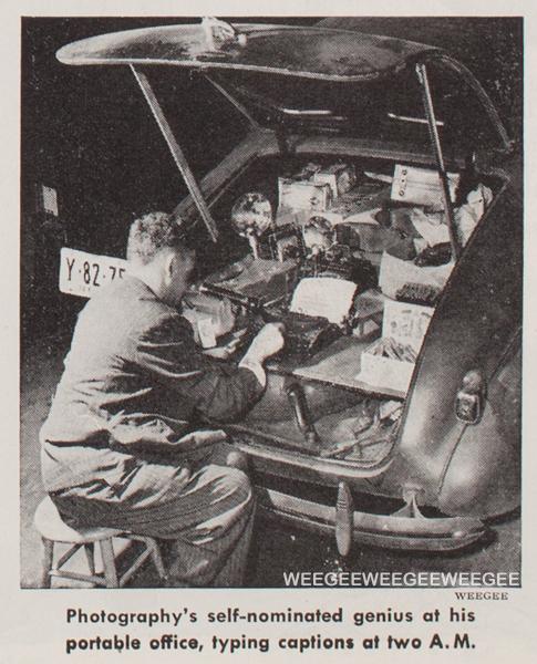 Weegee sitting behind his car typing